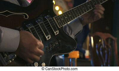 Guitarist plays on the electric guitar at the concert