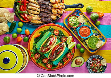 Mexican chicken and beef fajitas tacos in colorful table...
