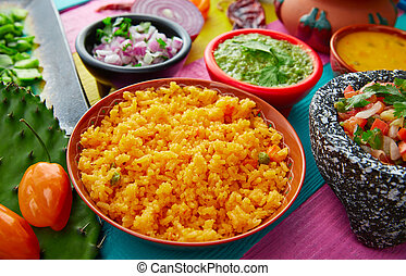 Mexican yellow rice with chilis and sauces in colorful...