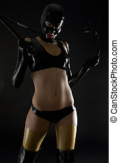 woman wearing latex clothes with whip