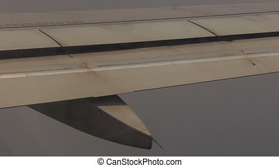 View Airplane Wing with Flaps above White Clouds - view of...