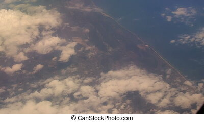 View Seacoast under Clouds from Airliner Window - panorama...
