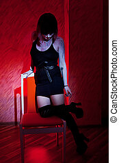 girl in stockings posing in chair against a red