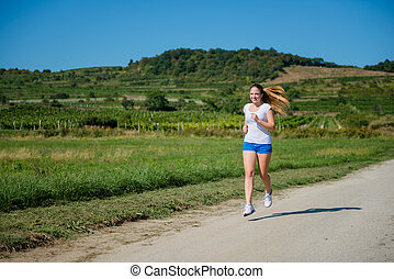 Jogging in nature - Beautiful young woman jogging in nature...