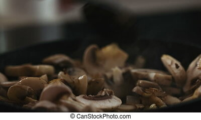 Spoon-mingled mushrooms and onions in a pan closeup
