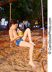 boy with coconut on the beach swing