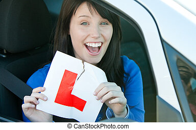 Happy brunette teen girl sitting in her car tearing a L-sign...