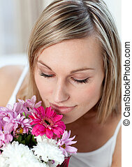 Beautiful woman smelling a bunch of flowers at home