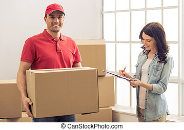 Moving to a new apartment - Attractive young woman is...