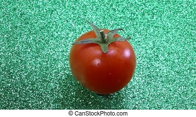 red tomato rotating in the green glitter background
