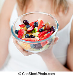 Close-up of a caucasian woman eating a fruit salad