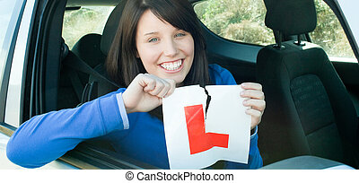 Smiling teen girl sitting in her car tearing a L-sign after...
