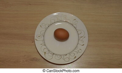 Chicken egg on a plate spinning - Chicken egg turns into a...