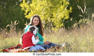 Mother and daughter listening to music on nature