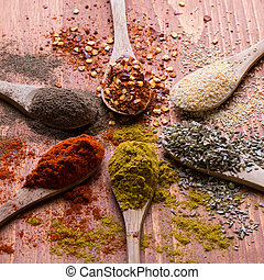 diferent color spices on wooden table - assortment of...