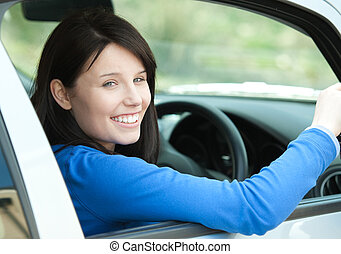 Portrait of a smiling woman driving - Portrait of a smiling...