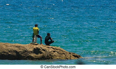 Backside Two Guys Stand on Rock against Azure Sea - MUI NE,...