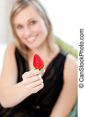 Jolly woman eating a strawberry