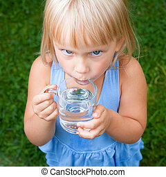 Child drinking water outdoors - High angle view shot of...