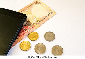 Indian money with mobile phone on white - Mobile phone with...