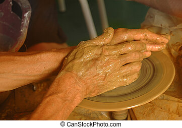 Hands of master on wheel of potter