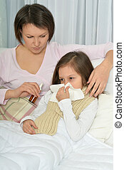 Sick little girl with mother in bed at home