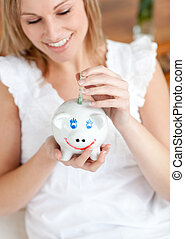 Attractive woman saving money in a piggy-bank