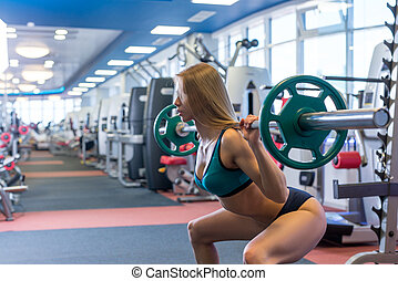 Beautiful young woman doing squats with barbell