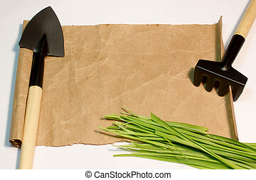 A sheet of paper and garden tools on white background