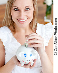 Bright woman saving money in a piggy-bank