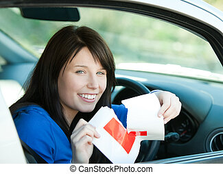 Charming brunette teen girl sitting in her car tearing a...