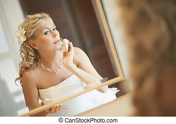 Gorgerous bride standing in front of mirror and fixing her...