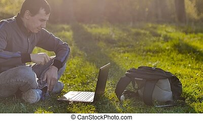 man student with laptop sitting on green grass lifestyle lawn sunlight