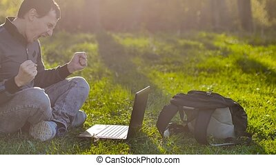 man student surprise joy with laptop notebook sitting on green grass lifestyle lawn sunlight