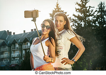 Selfie in the steet at summer - Two wild young women taking...