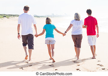 loving family - a back view of a loving family walking on...