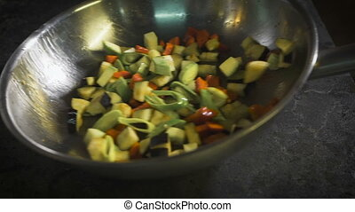 chef interfere in the pan vegetables. Kitchen cafe or...