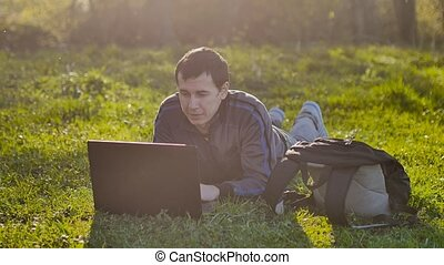 man student with laptop sitting on green grass lawn...