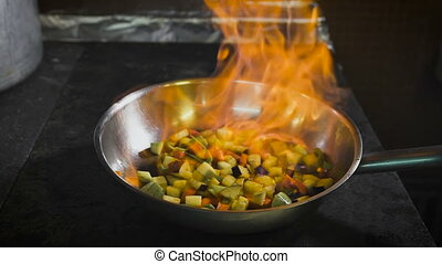 Chef frying vegetables. Cognac is ignited in the pan. Open fire in the kitchen