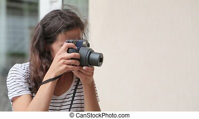 Girl makes the photo on the old-school camera and smiling.