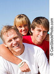 father and kids - a happy father with his two teen kids on...