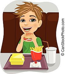 young boy eating cheeseburger with french fries and coke in...