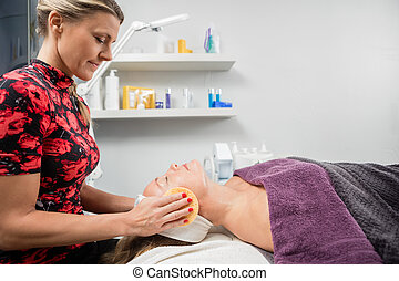 Beautician Cleansing Client's Face With Sponge