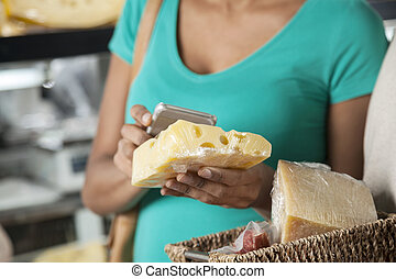 Woman Scanning Cheese Through Cell Phone In Grocery Shop