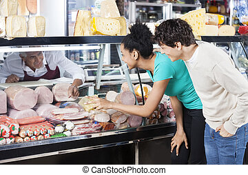 Couple Choosing Product From Display Cabinet While Salesman...