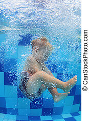Little child swimming with fun and diving down in pool -...