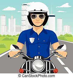 confident policeman with sunglasses riding motorcycle through the city streets