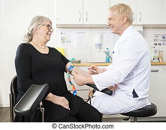 Smiling Doctor Collecting Senior Patient's Blood For Test In...