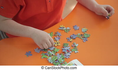 boy collects a puzzle. Full HD