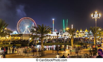 Main square and lake in Global Village with crowd and attractions timelapse in Dubai, UAE